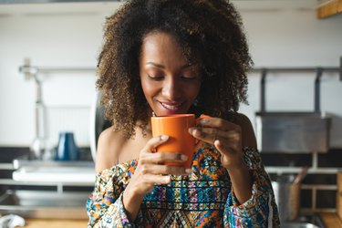 woman drinking coffee from an orange mug at home in her kitchen