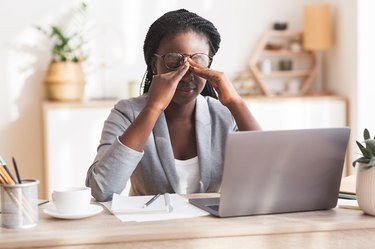 woman working at home and rubbing her eyes because she can't focus