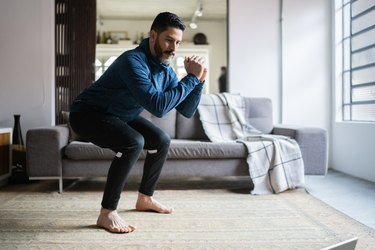 Mature man with dark hair and beard doing a squat exercise in his living room