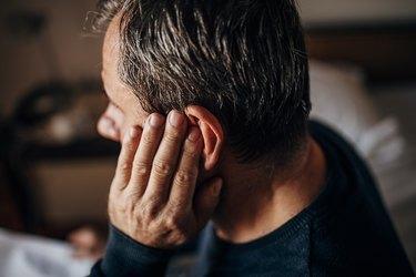 older man covering ear because of pulsatile tinnitus