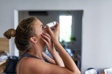 woman putting eye drops in her eyes