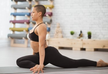 athletic woman doing pigeon pose on a black yoga mat