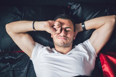 A man waking up in bed and rubbing his eyes because of eye discharge
