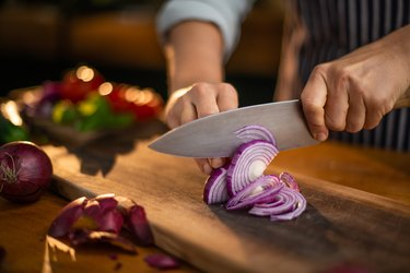 view of hand Cutting red onion on wooden board