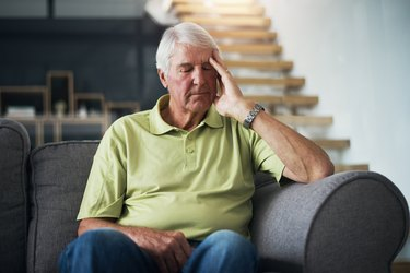 An older man sitting on the couch feeling tired