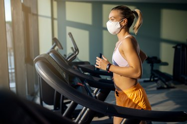 woman with face mask running on treadmill in health club.