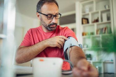 Older man taking his blood pressure at home using a blood pressure cuff