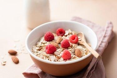 bowl of muesli with fresh raspberries and raw almonds on linen napkin