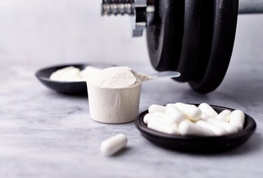 Scoop of creatine powder with capsules and a dumbbell on marble