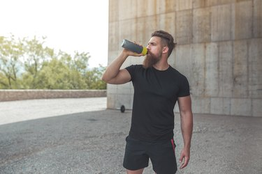 muscular athlete drinking a protein shake to build muscle