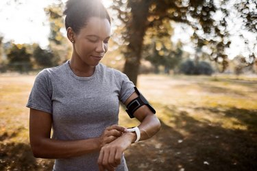 black woman outside, looking at running watch to track her running split times