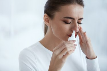 Beautiful Woman Using Nasal Spray for a sinus infection