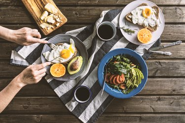 Hand forking into fried eggs (one of the foods that give you energy) on toast with salad and coffee on wooden table