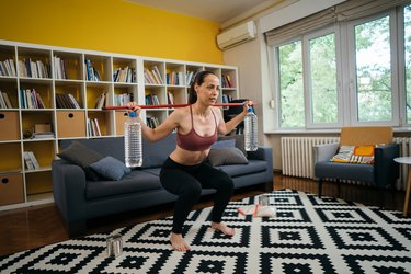 woman performing a squat with slosh pipe in living room
