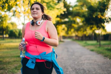 a woman in a pink top running outside with a water bottle, avoiding pre-run mistakes