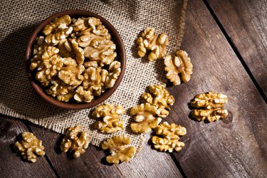 Organic omega-3-rich walnuts in bowl and scattered on wooden table