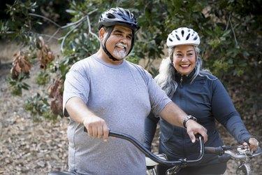 adult couple biking outside wearing helmets