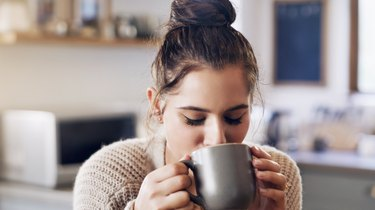 A woman drinking coffee, which makes constipation worse
