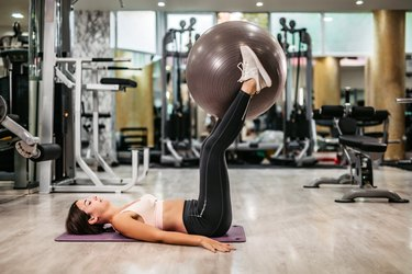 woman doing stability ball leg raises in the gym