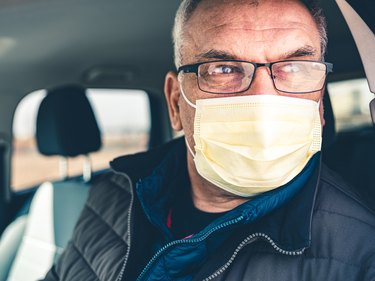 COVID-19, Mature man wearing disposable face mask and eyeglasses