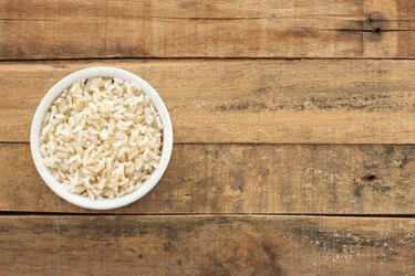 Bowl of brown rice on wood table, as an example of one way to eat carbs at night for weight loss