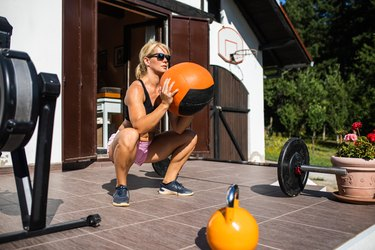 woman outside doing squat variations with a medicine ball, barbell and kettlebell