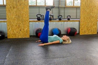 blonde woman wearing blue leggings and doing leg raise ab exercise