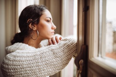 A woman with depression looking out the window of her home