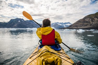 woman paddling a kayak on an icy bay in Alaska exploring glaciers