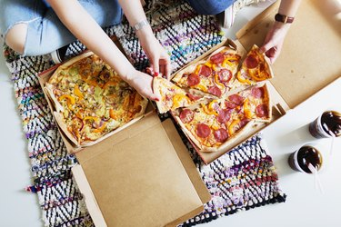 High angle view of friends eating pizza with cola in new home
