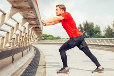 man in a red shirt outside doing a standing calf stretch for the back of the knee