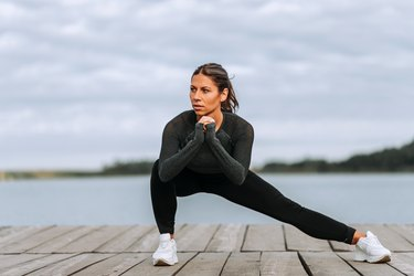 Front view of a fit woman doing side lunges near the river.