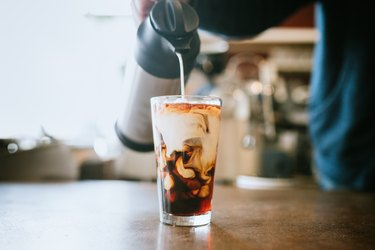 Barista Pours Milk Into Cold Brew Coffee