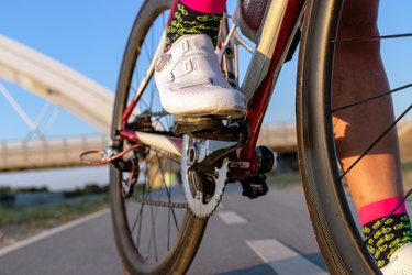 close up of white cycling shoes on a cycling riding a bike