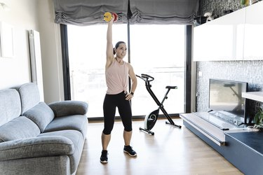 Young woman lifting a dumbbell at home - Stock photo