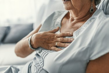 older woman with gerd symptoms, with her hand on her chest from heartburn