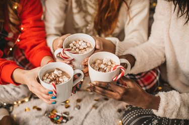Womens' hands holding hot chocolate with marshmallows and candy canes