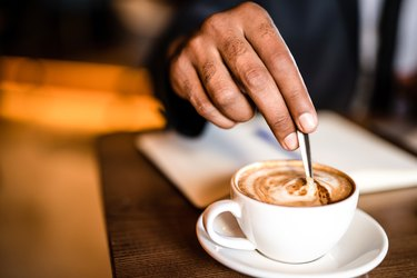 Man's hand mixing coffee latte with spoon