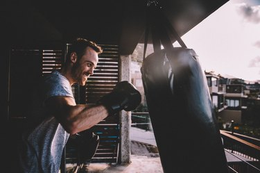 Young man doing an intense boxing workout at home on balcony, triggering exercise-induced oxidative stress