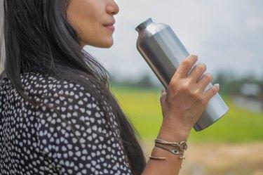 Asian Woman Drinking Water from Reusable Metallic Water Bottle