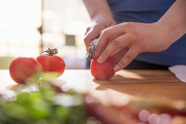 Hands of woman slicing tomato at kitchen counter