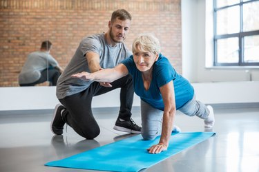 Senior woman exercising with trainer at rehab