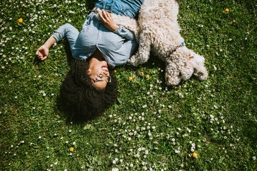 Woman Rests in the Grass With Pet Poodle Dog