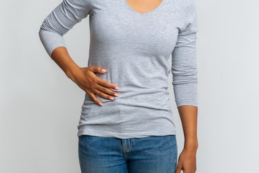 African woman suffering from liver pain, cropped