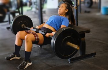 Asian woman doing a barbell hip thrust at the gym