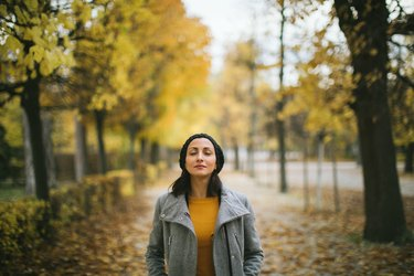 A woman practicing color breathing during a walk in the park