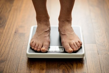 Close-up of weighing on mechanical bathroom scale. Feet standing on weight scale laying on wooden flooring.