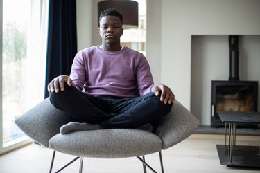 A man meditating at home as a way to promote heart health
