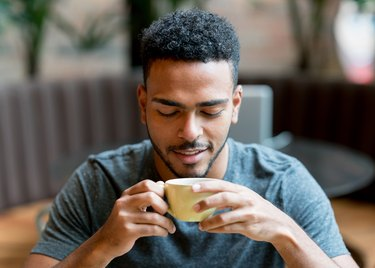 Happy man drinking a cup of coffee at a cafe