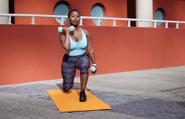 Shot of a young woman on a gym mat doing a dumbbell lunge to curl combination exerice
